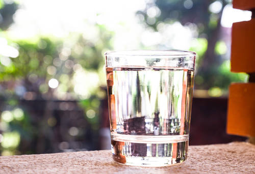 Refreshing purified water in transparent glass  against with greeneries background