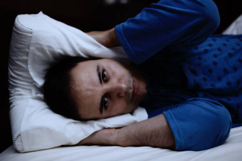 Portrait of a man trying to sleep in his bed