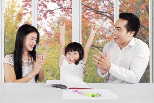Two parents giving applause to their daughter after finishing her homework