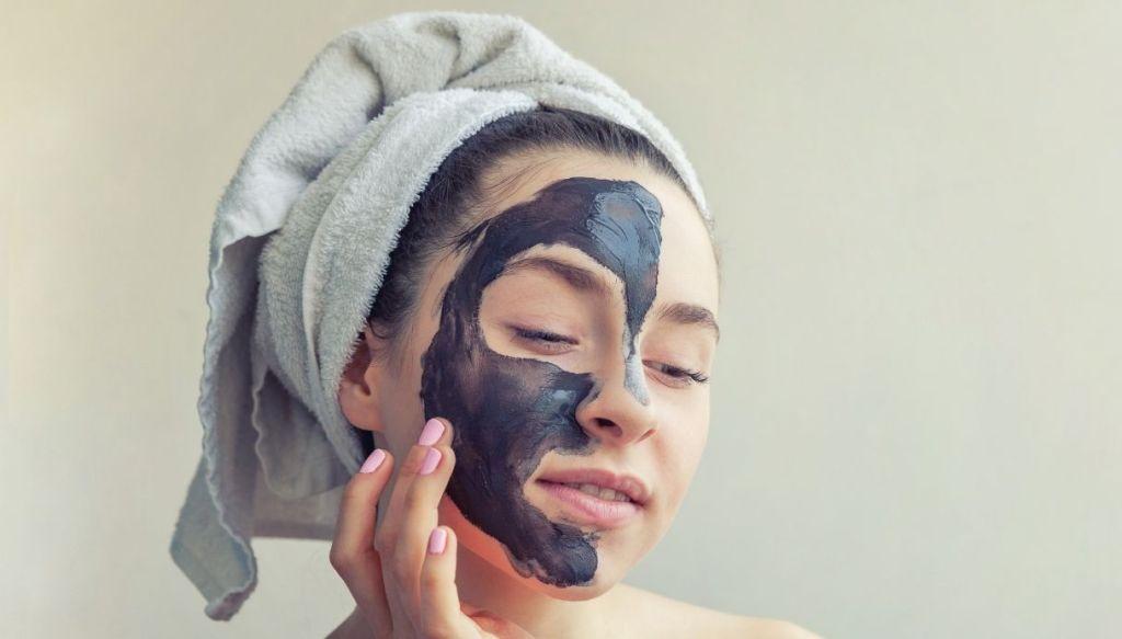 Donna applica maschera nera sul viso