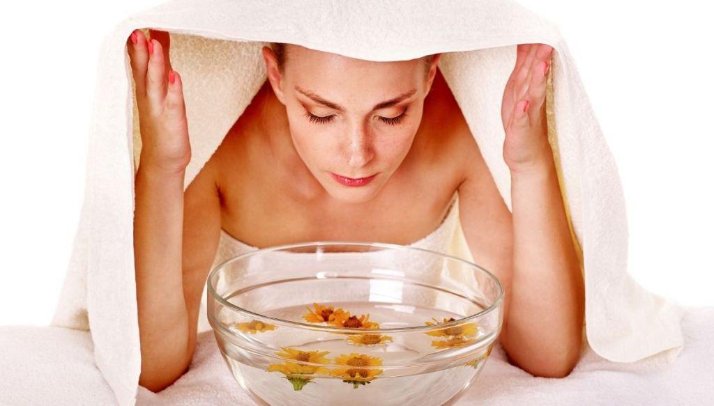 Donna con asciugamano i testa fa sauna facciale con vapori caldi aromatici