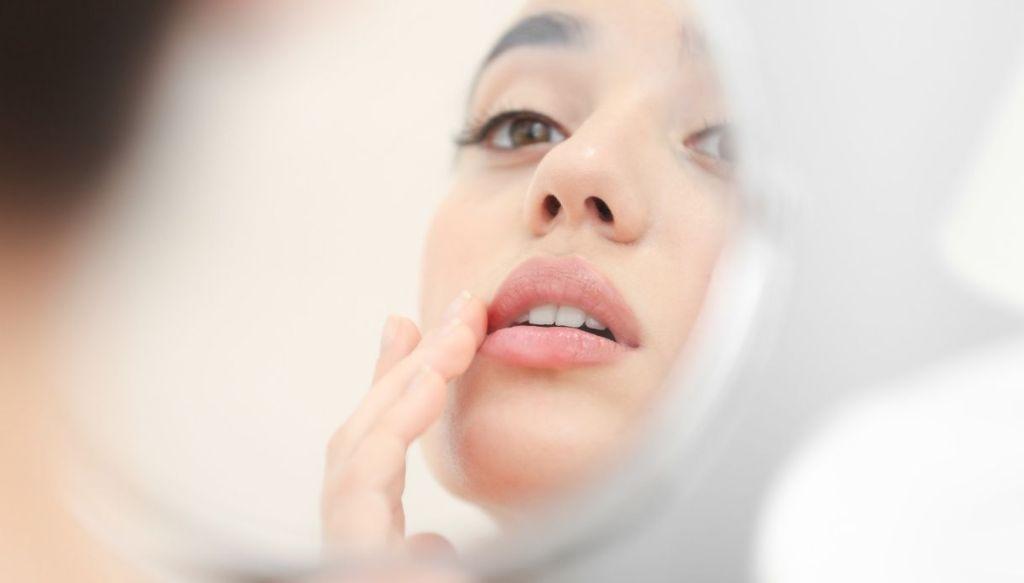 donna riflessa allo specchio si tocca le labbra