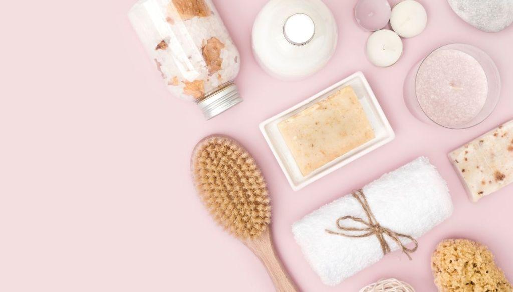 superficie rosa con spazzola, asciugamano, spugna, sali da bagno, sapone, candele, bagnoschiuma