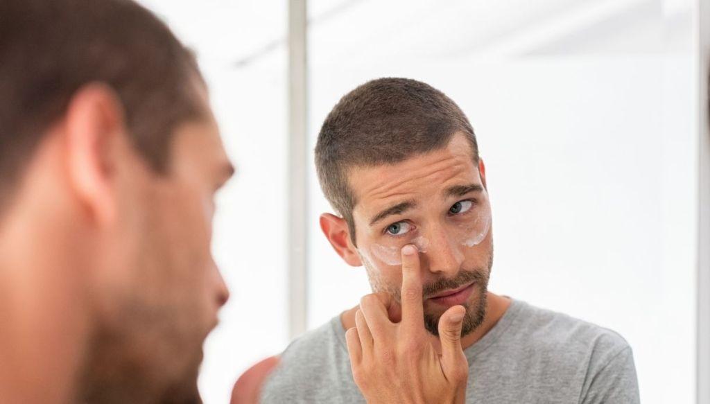 Uomo che si applica crema contorno occhi allo specchio