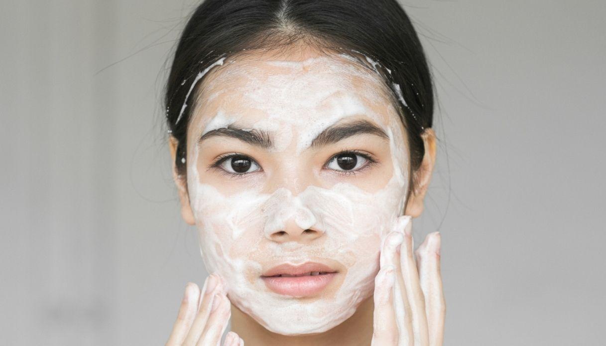 ragazza asiatica con sapone e schiuma sul viso