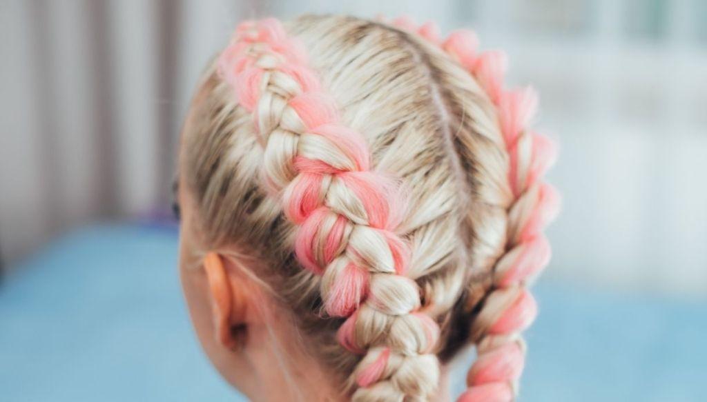 Ragazza bionda di spalle con tracce boxer braids rosa