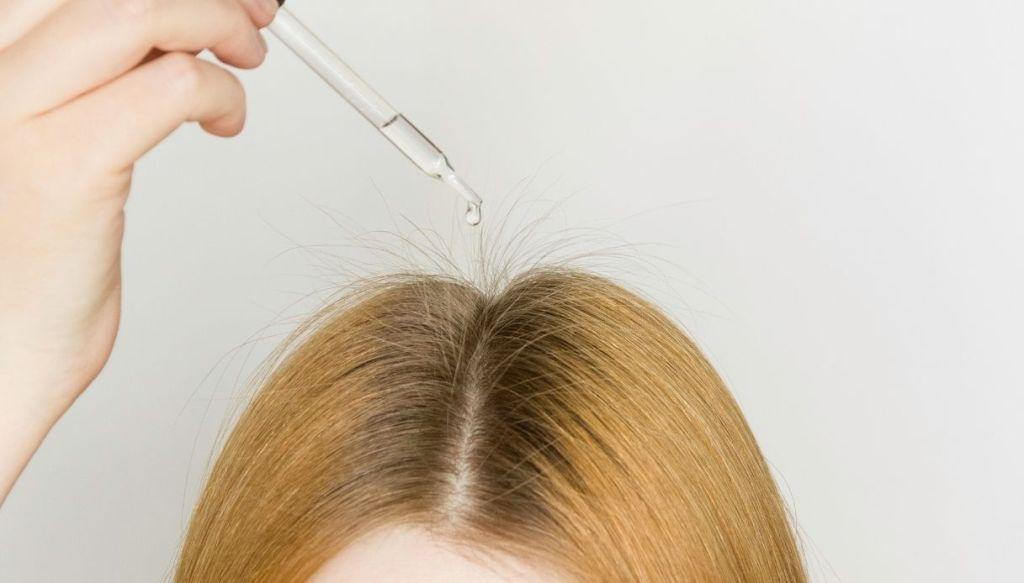 ragazza applica gocce sulla riga centrale dei capelli biondi con ricrescita