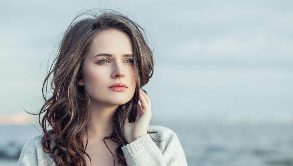 ragazza giovane guarda altrove e si tocca i capelli con sfondo nuvoloso