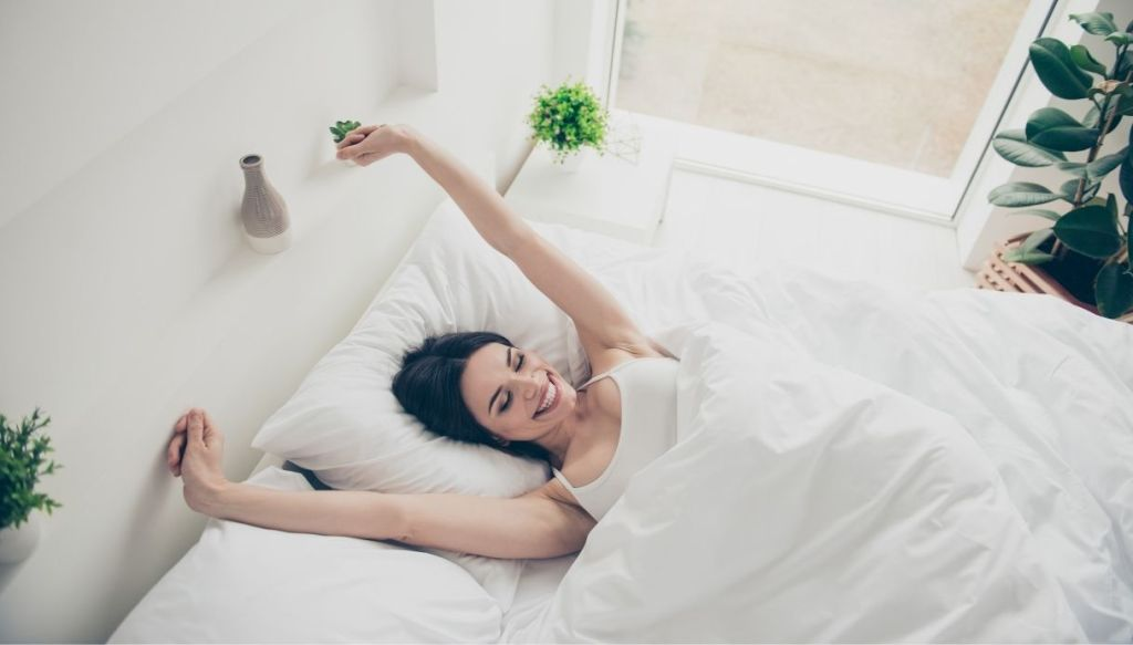 Donna mora sorridente braccia alzate letto lenzuola bianche camera luminosa