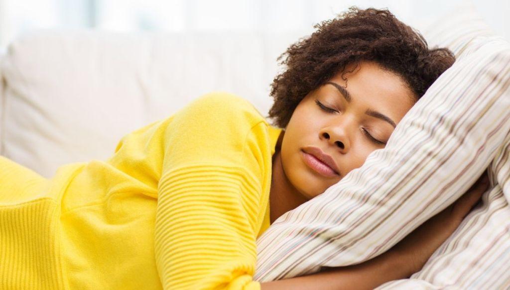 giovane donna nera riccia maglione giallo dorme su cuscino con federa a righe