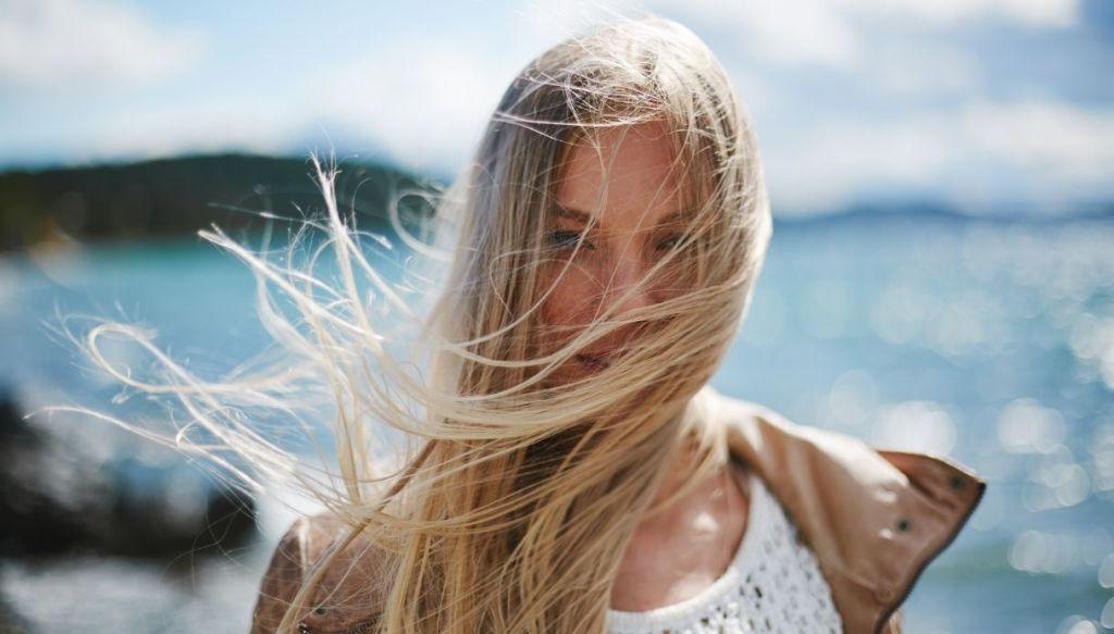 donna capelli biondi davanti al viso per il vento e paesaggio di mare