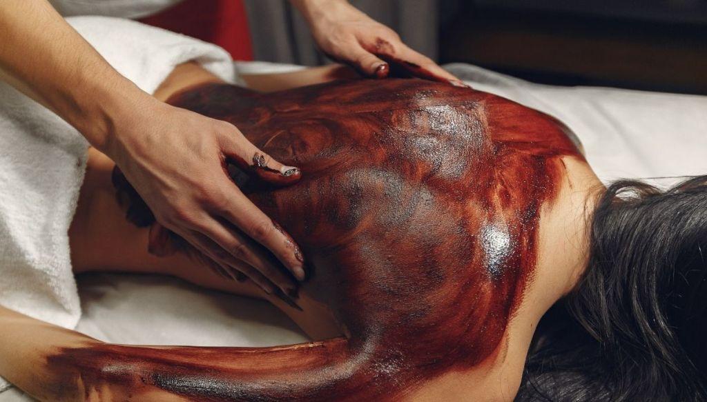 donna sdraiata di spalle viene massaggiata da mani maschili con impacco marrone al cioccolato