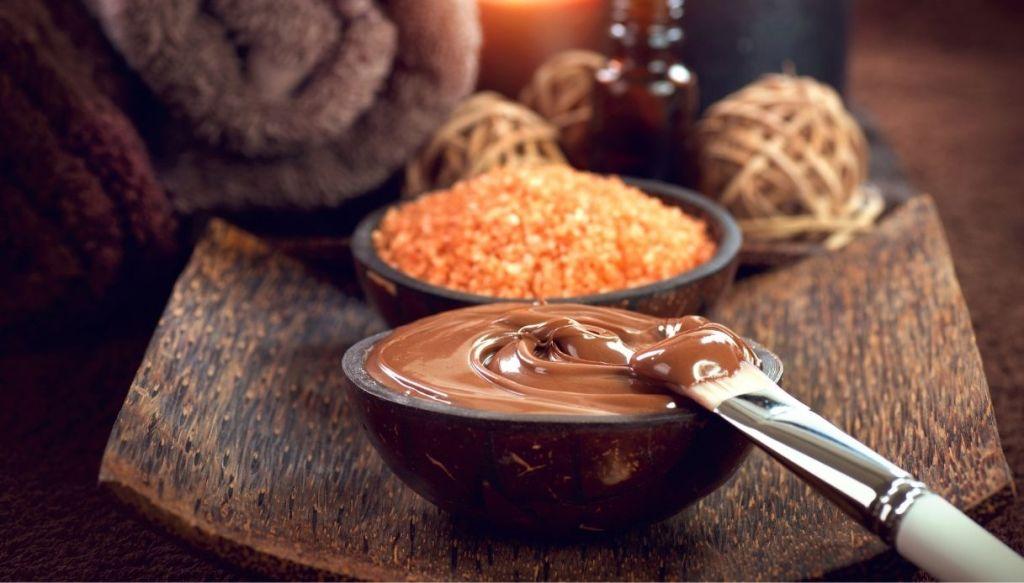 ciotola di legno con crema impacco al cioccolato e pennello e ciotola con zucchero e accessori in legno