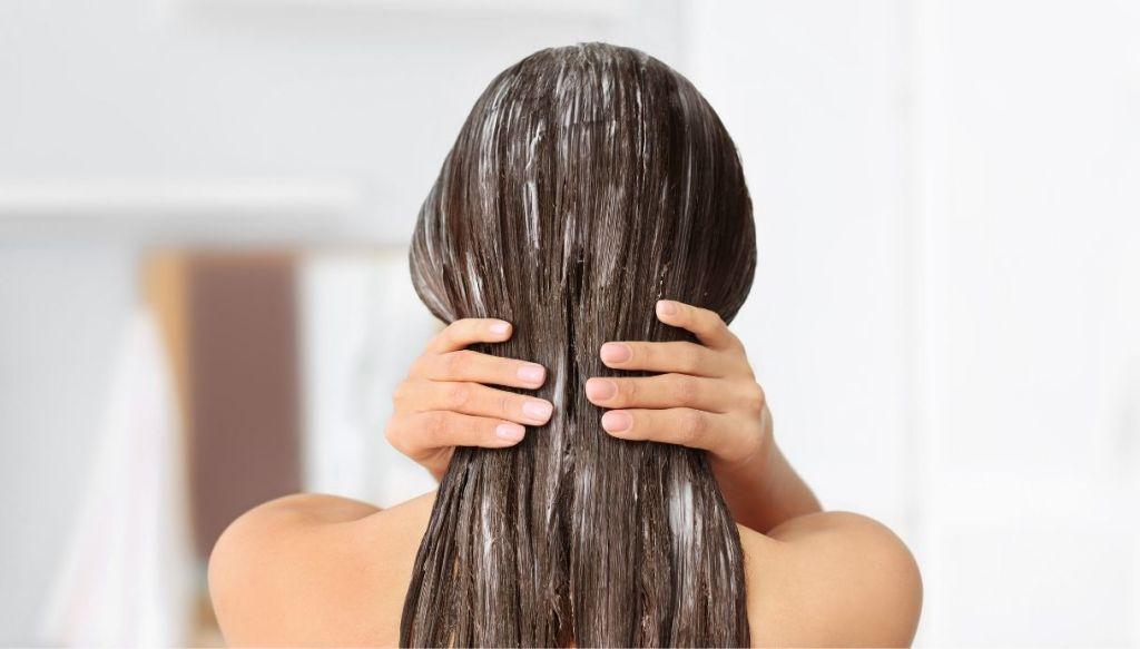 donna mora di spalle con le mani si tocca i capelli con applicata una maschera