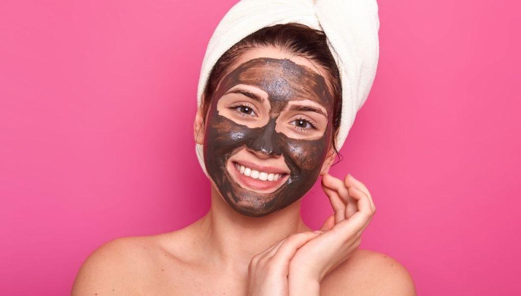 donna sorridente con turbante bianco e maschera viso marrone al cioccolato su sfondo rosa