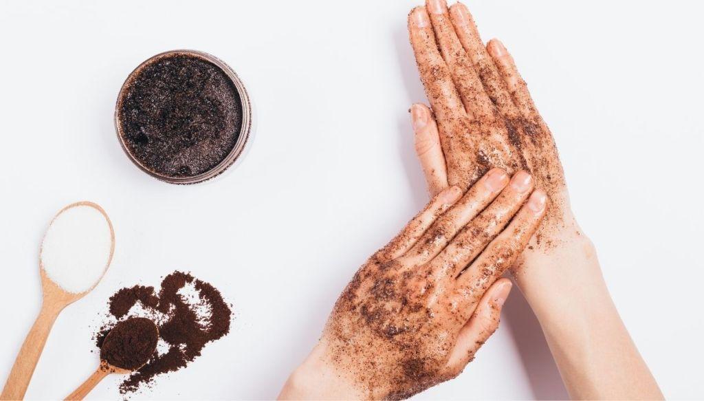 mani si spalmano scrub marrone al caffè e zucchero su sfondo bianco con cucchiaini di zucchero e caffè