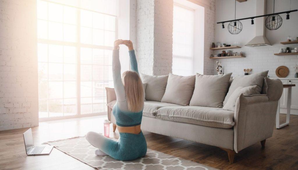 giovane ragazza bionda completo sportivo azzurro stretching in salone luminoso con divano grigio