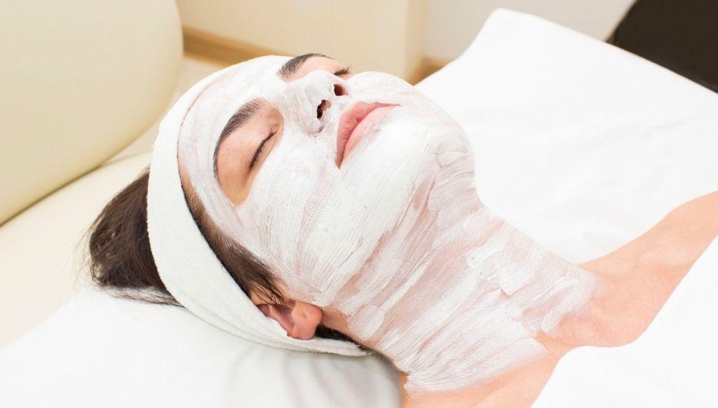 giovane donna mora sdraiata con fascia nei capelli e maschera bianca su viso e collo