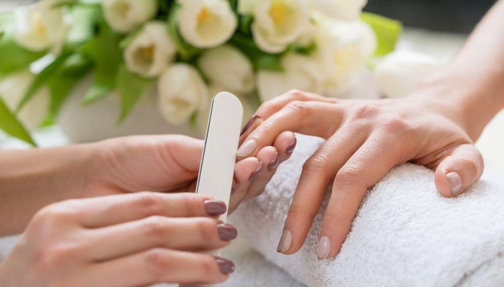 mani eseguono manicure e limatura unghie