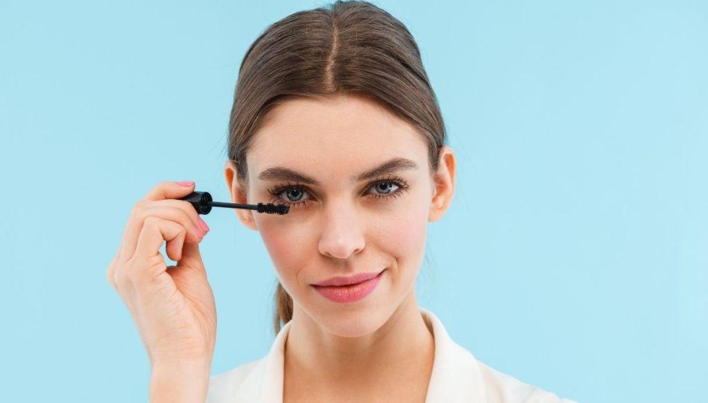 sfondo azzurro donna con coda e riga centrale capelli applica il mascara agli occhi