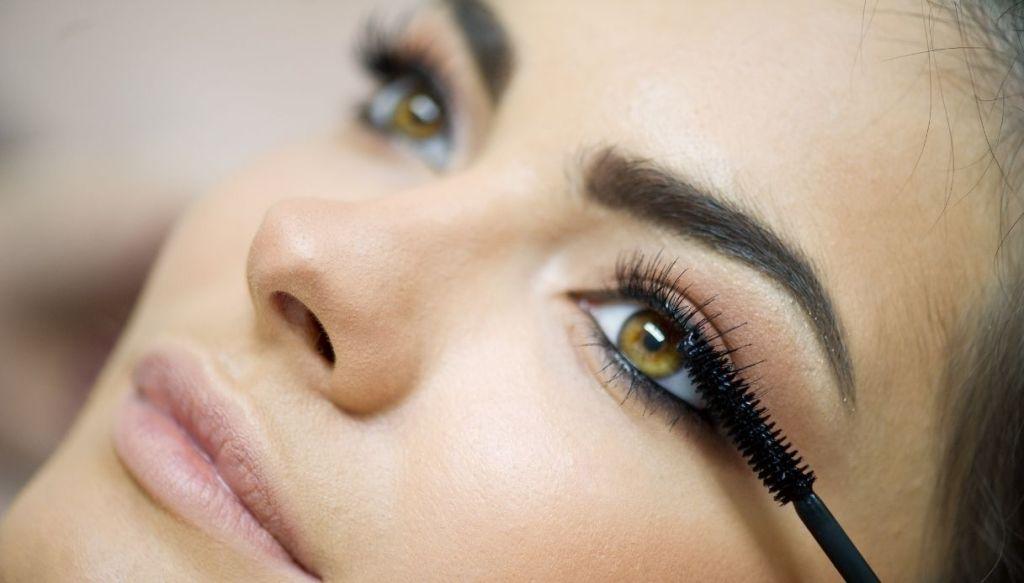 Primo piano ragazza occhi verdi trucco applicazione mascara