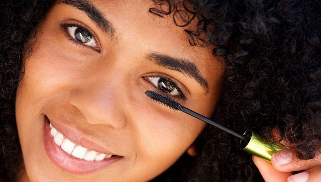 ragazza nera mulatta afro capelli ricci sorridente applica mascara