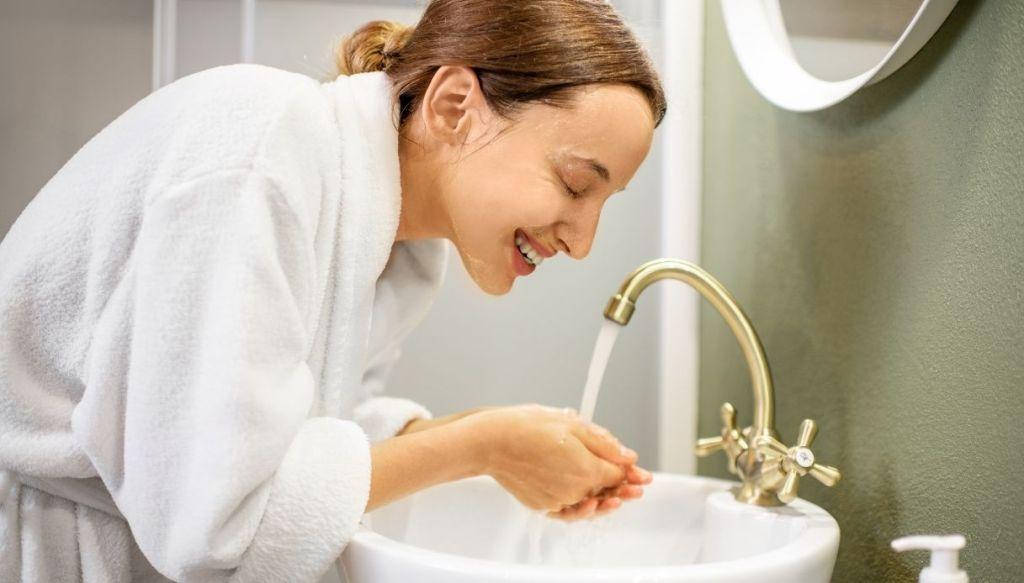 donna in accappatoio si lava la faccia