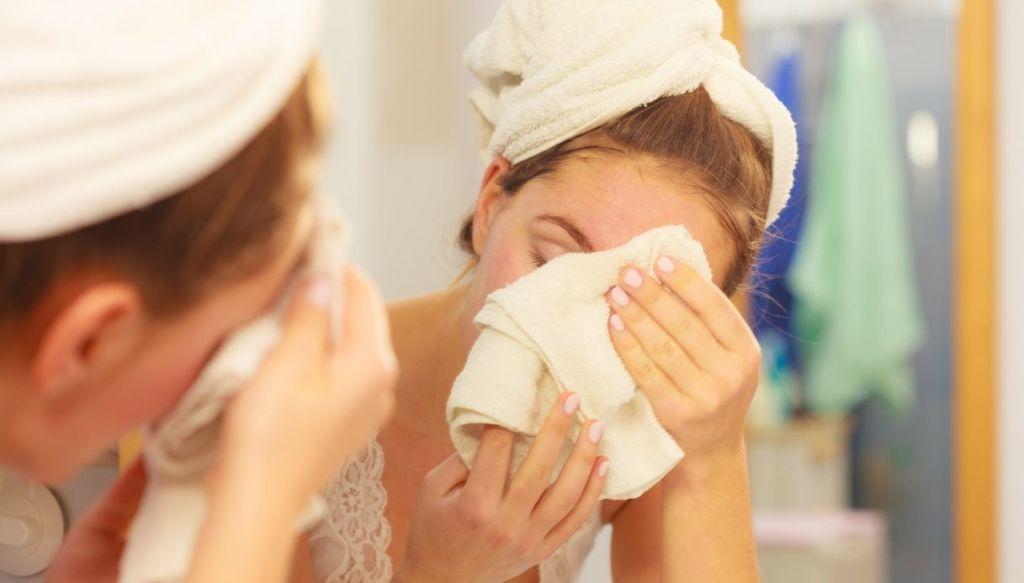 donna allo specchio con turbante si lava e asciuga il viso
