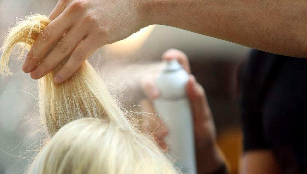 mano spruzza lacca shampoo secco su ciocca capelli biondi