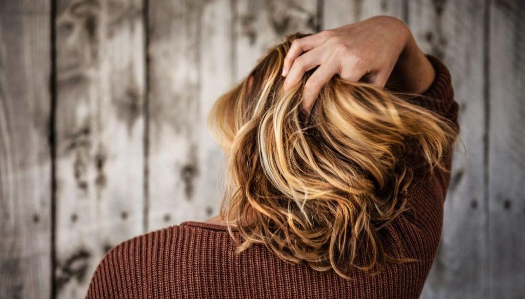 Donna si tocca i capelli biondo caramello con meches