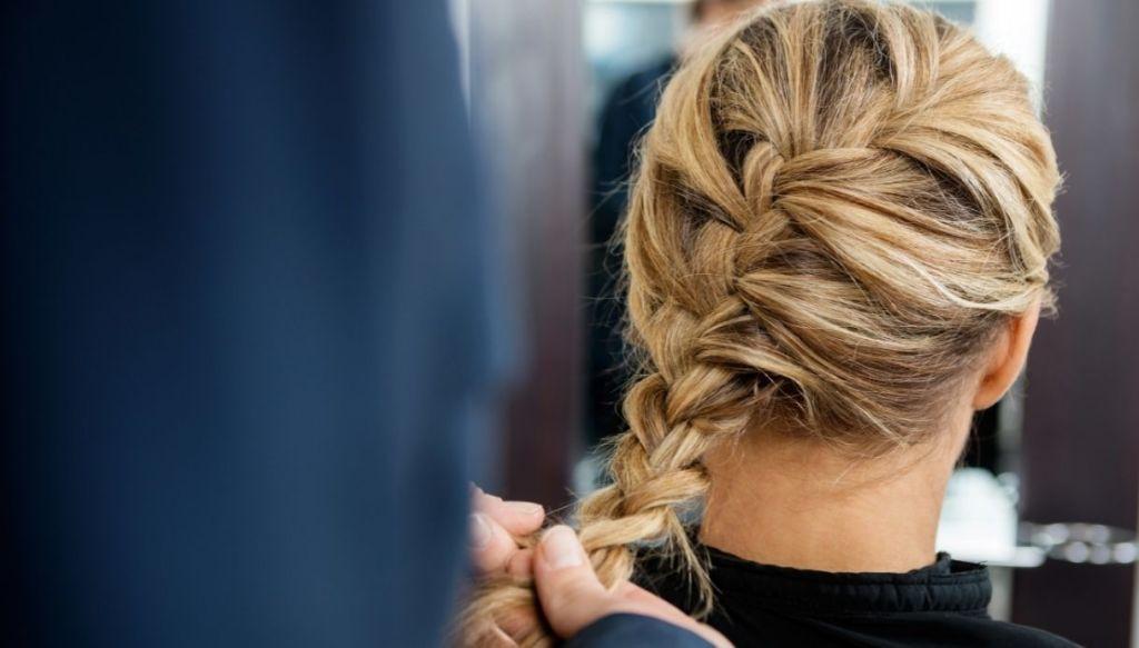 donna bionda di spalle acconciatura treccia voluminosa