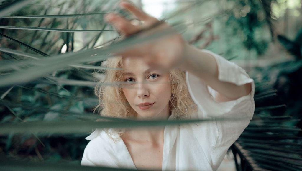 ragazza bionda camicia bianca capelli biondi nascosta dietro pianta