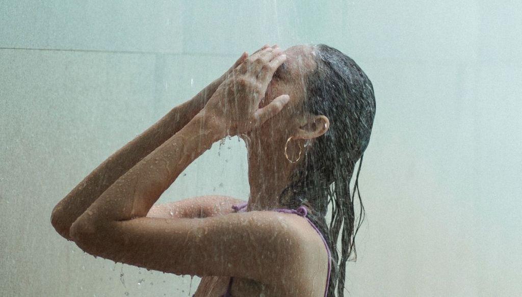 ragazza in costume viola con occhi chiusi lava sciacqua capelli sotto doccia