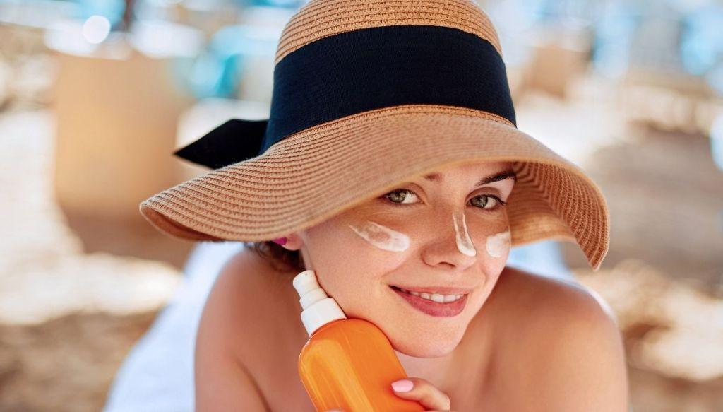 donna con cappello paglia crema solare viso