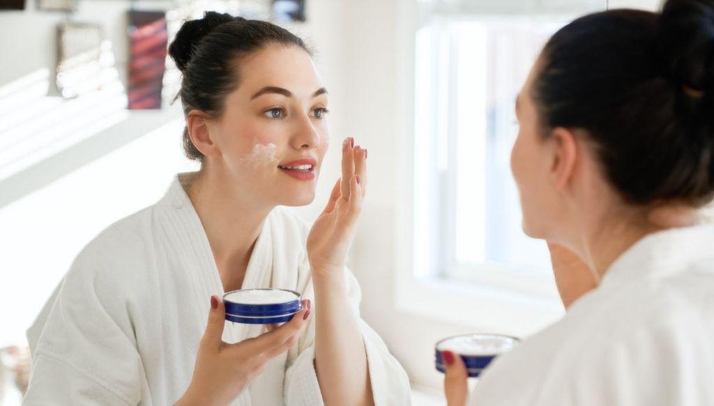 donna applica crema viso doposole allo specchio