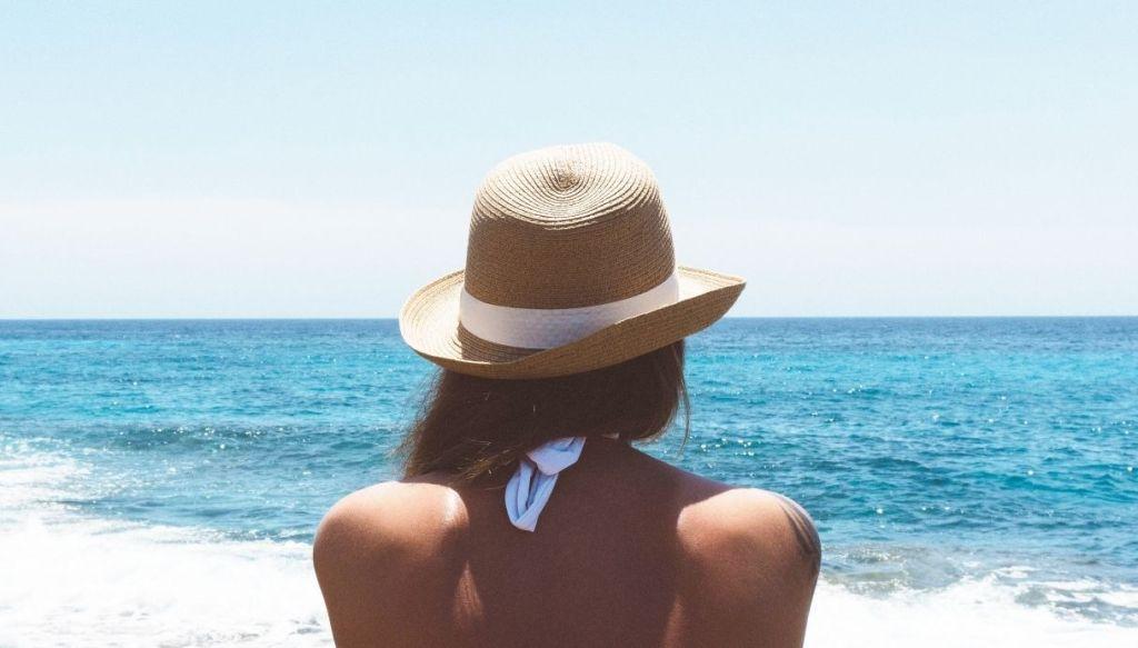 ragazza di spalle prende il sole con cappello abbronzatura dorata