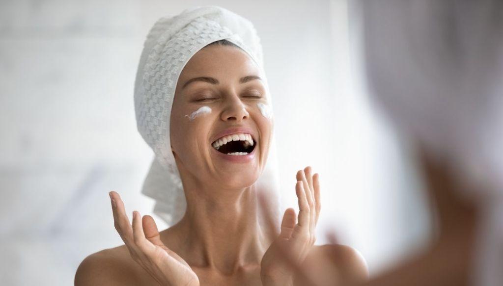 Donna con turbante che ride applica crema viso