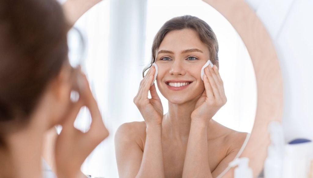 Donna allo specchio applica maschera viso
