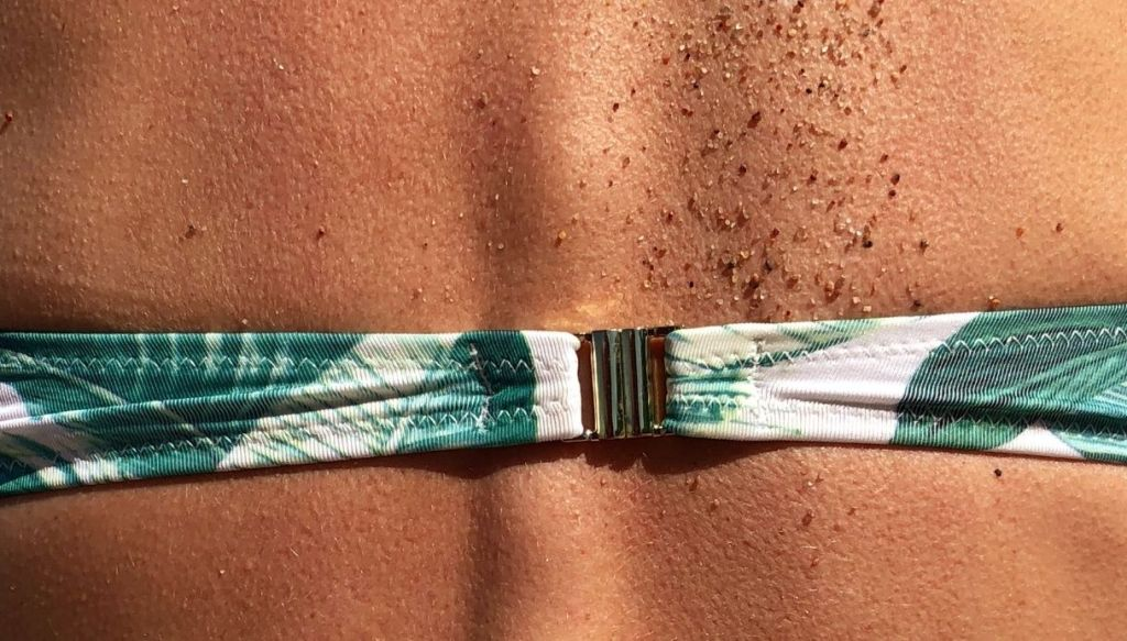 schiena donna abbronzata costume da bagno colorato