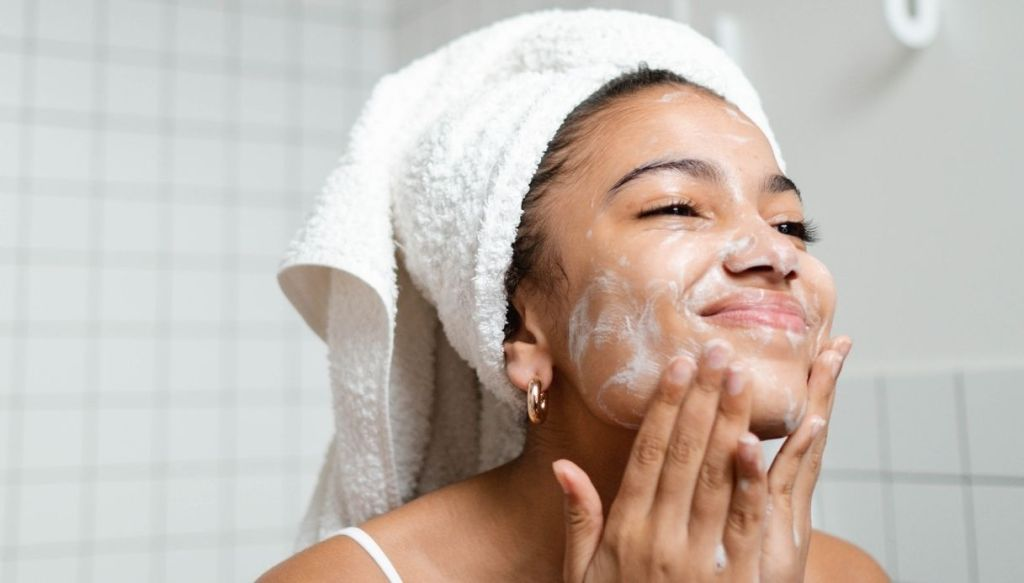 Ragazza nera turbante capelli si lava il viso sapone schiuma