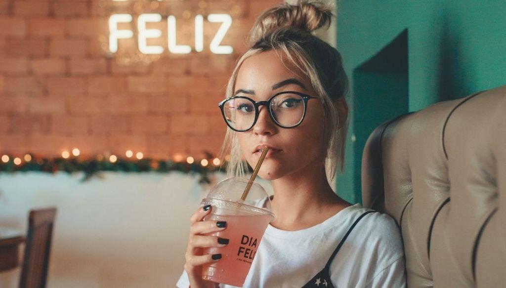 ragazza bionda crocchia beve una bibita fresca