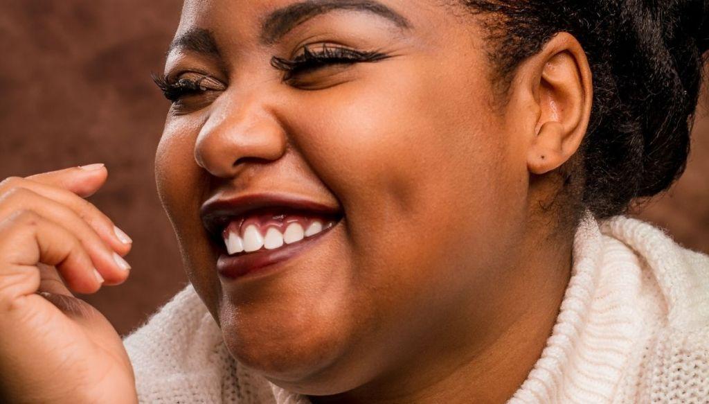 donna nera sorridente trucco labbra scure rossetto bordeaux