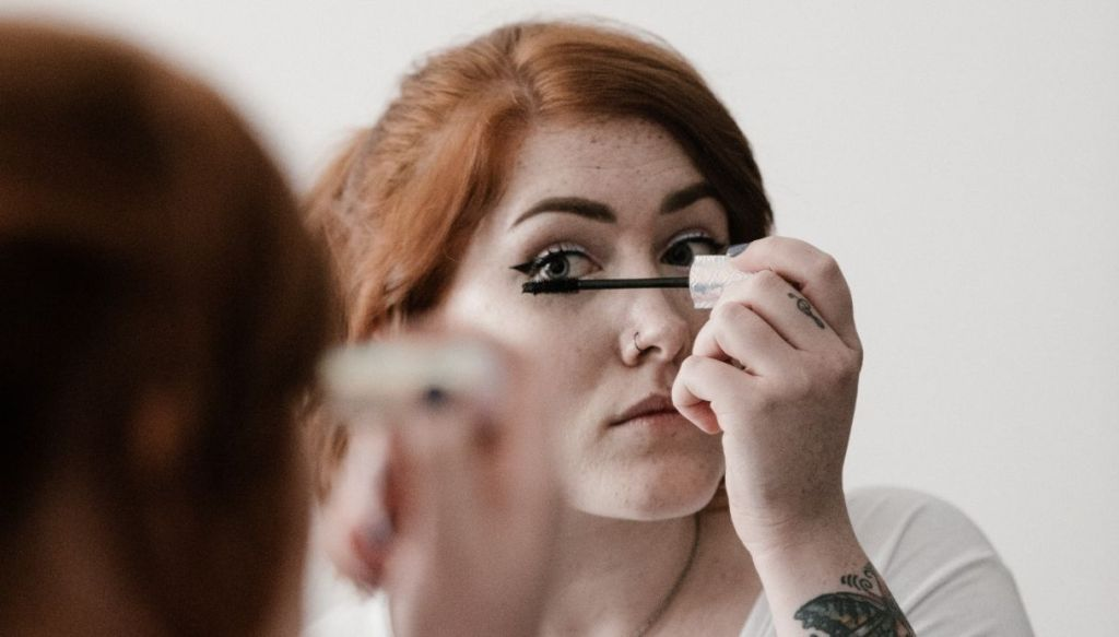 ragazza rossa mascara allo specchio