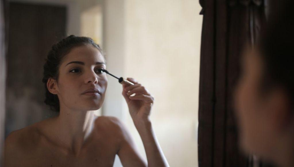 ragazza mora applica mascara allo specchio