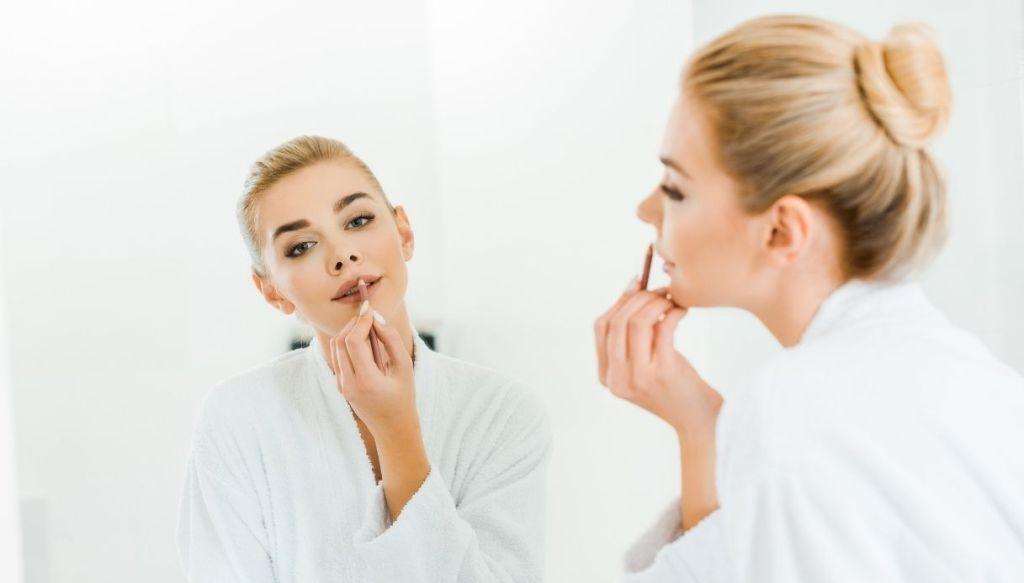 ragazza bionda applica matita labbra allo specchio