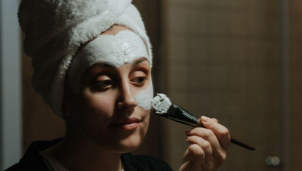 ragazza turbante capelli applica maschera viso